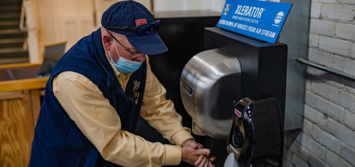 A man uses the XLERATOR Mobile Hand Hygiene Station